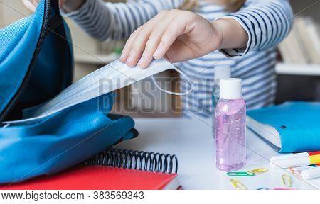 Little Girl Packing Blue Backpack In Kidss Room. Face Mask, Bottle Of Sanitizer, Stationery, Pens, M