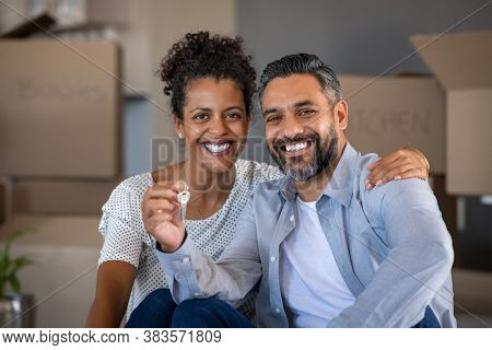 Middle aged multiethnic couple embracing and holding house keys with carboard boxes behind them. Portrait of indian man and african woman showing house keys while looking at camera after relocation.