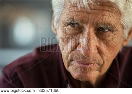 Thoughtful senior man sitting on couch looking away with copy space. Depressed sad man thinking at home. Elderly pensive senior suffering from alzheimer disease.