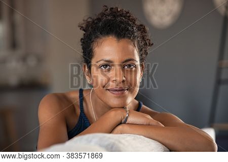 Confident indian woman relaxing on couch at home. Thoughtful smiling middle eastern girl sitting on sofa and looking at camera. Portrait of satisfied african woman daydreaming with copy space.