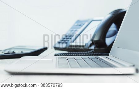 Business And Communications. Laptop And Voip Phone In The Office, Close Up Of Hand. Finance Graphs.
