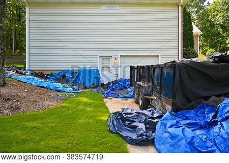 Tarps And Dumpster Placed At Home Owners House As Contractor Starts Removing Old Roof In Preparation