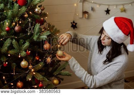 Stylish Young Woman In Santa Hat Decorating Christmas Tree With Shiny Golden Ornament In Modern Room