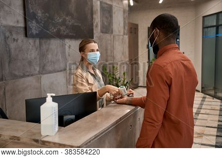 Young Woman Wearing Medical Mask Standing At Reception In The Office And Using Infrared Thermometer,