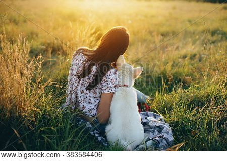 Woman Sitting With Cute White Puppy And Looking At Sunset In Summer Meadow. Stylish Girl Relaxing Wi