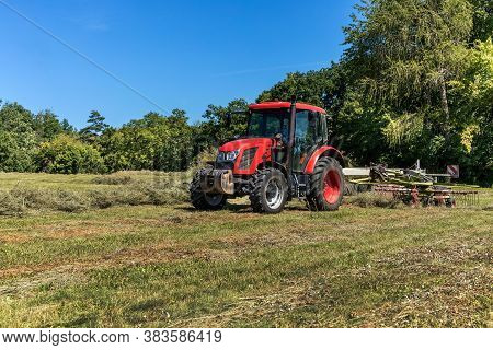 Modern Red Tractor In The Agricultural Field. Work On An Organic Farm. Haymaking. Tractor On A Green