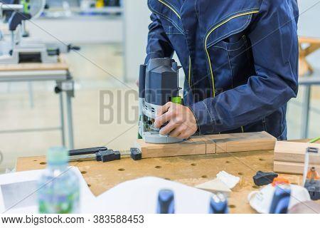 Professional Man Carpenter Using Electric Sander To Polish Wood On Rough Workbench At Workshop. Desi
