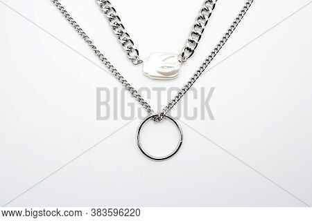 Bijouterie. Two Silver Chains And A Beautiful Shiny White Gem On A White Background. Jewelry Concept
