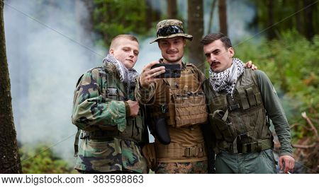 team of soldiers and terrorist taking selfie with smartphone in the forest