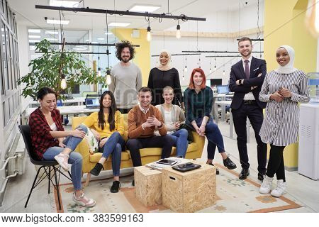 Business team portrait at modern startup office, standing together and posing for photo motivated and creative successful diverse employees group