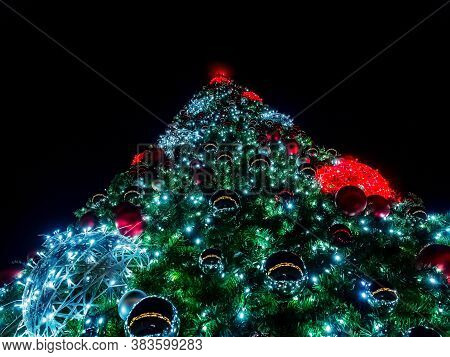 A Giant Christmas Tree Decorated With Many Balls And Garlands Glows In The Night. Bottom Up View
