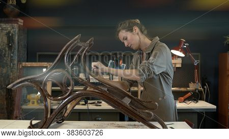 Restoration Of Wooden Rocking Chair In A Workshop. A Working Female Carpenter Peels Off Paint From R