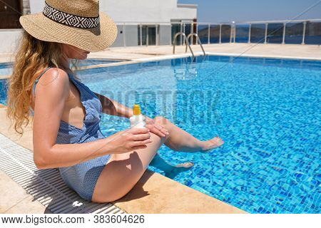 Young Woman In Straw Hat Applying Sun Protection Cream Suntan Sunscreen Lotion Near Swimming Pool At