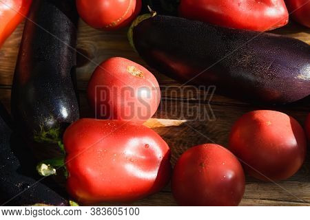 Farm Tomatoes, Bell Peppers, Eggplants And Greens Lie On A Wooden Surface. Concept Of Biological, Bi
