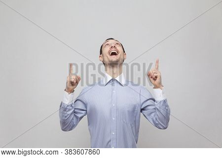 Portrait Of Surprised Handsome Bristle Businessman In Classic Blue Shirt Standing And Pointing At Do