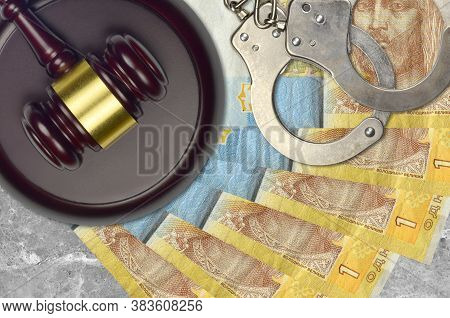 1 Ukrainian Hryvnia Bills And Judge Hammer With Police Handcuffs On Court Desk. Concept Of Judicial