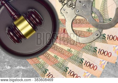 1000 Guyanese Dollars Bills And Judge Hammer With Police Handcuffs On Court Desk. Concept Of Judicia