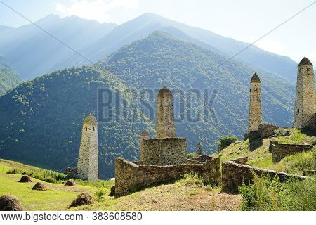 Old Stone Towers In Green Mountainous Terrain. Ancient Stone Buildings Of Old Town Located On Green
