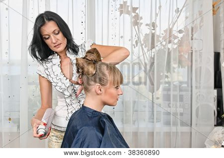 woman making a coiffure in hairdressing saloon poster