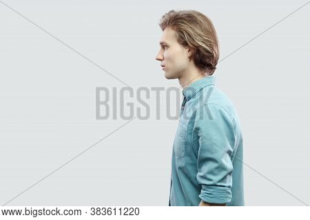 Profile Side View Portrait Of Handsome Long Haired Blonde Young Man In Blue Casual Shirt Standing An