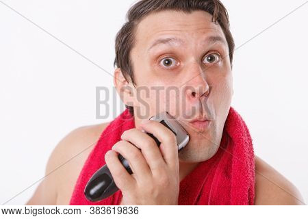 Isolated On A White Background: A Man Shaves His Stubble. The Guy Cleans His Beard With An Electric