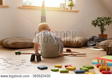 Boy Playing On A Sunny Day In A Room With A Train Surrounded By Other Toys.