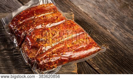 Vacuum Packed Meat On A Wooden Background. Banner, Menu, Recipe, Place For Text.