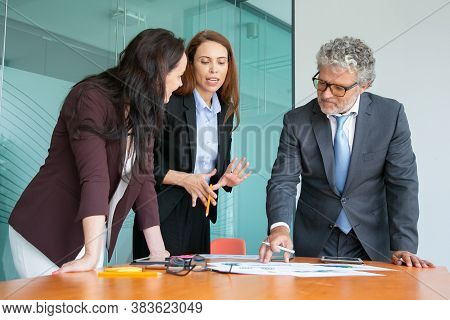 Confident Businesspeople Discussing Project Together. Professional Colleagues Standing Near Table Wi