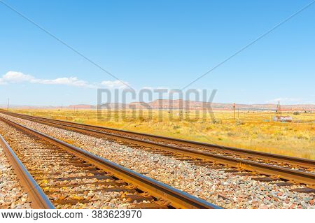 Diminishing Perspective Of Railway Tracks Through Flat Plains Of New Mexico With Distant Mesa Landfo