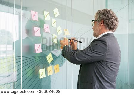 Concentrated Senior Businessman Writing On Sticker With Black Marker. Colorful Memo Notes Stuck On G