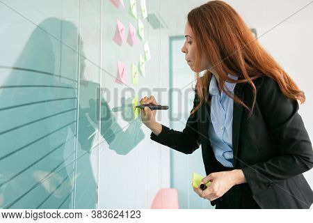 Concentrated Red-haired Businesswoman Writing On Sticker With Marker. Colorful Memo Notes Stuck On G