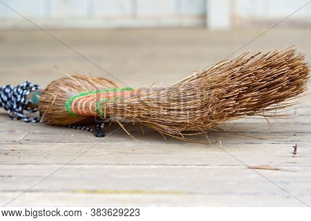 Close Up Of An Old Discarded Straw Broom Left On The Floor It Swept