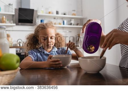 Partial View Of African American Mom Pouring Cornflakes Into Bowl Near Daughter Having Breakfast