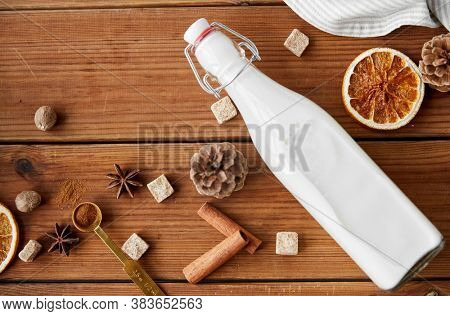 christmas and seasonal drinks concept - bottle of milk, aromatic spices and sugar on wooden background