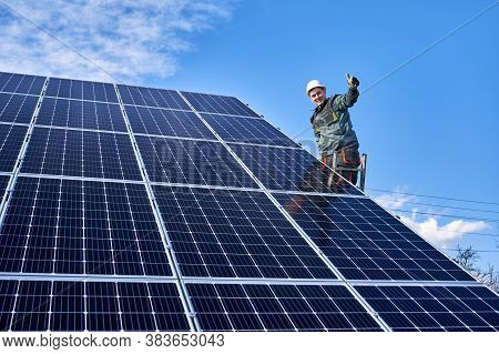 Smiling Worker, Installing Solar Batteries. Male Engineer Standing On Ladder At Solar Plant Against