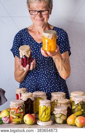 Senior Mature Woman Holding In Hands Jar With Homemade Preserved And Fermented Food. Variety Of Pick