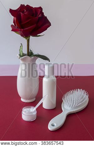 White Hair Comb, Unlabeled Shampoo Bottle, Hair Care Products And Red Rose In White Vase On The Tabl