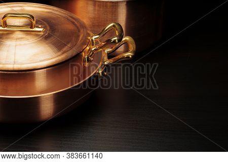 Shiny Vintage Copper Cookware Over Dark Background