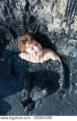 Boy Sitting In Mud