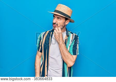 Middle age handsome tourist man on vacation wearing shirt and hat over blue background thinking concentrated about doubt with finger on chin and looking up wondering