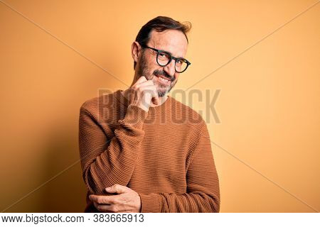 Middle age hoary man wearing brown sweater and glasses over isolated yellow background with hand on chin thinking about question, pensive expression. Smiling and thoughtful face. Doubt concept.