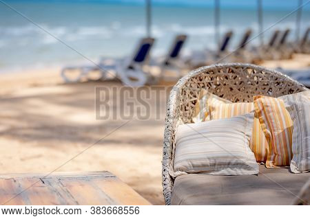 Striped Pillows On Comfortable Rattan Chair On The Beach. Summer Vacation And Relaxation Concept
