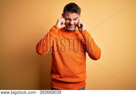 Young handsome man wearing orange casual sweater standing over isolated yellow background covering ears with fingers with annoyed expression for the noise of loud music. Deaf concept.
