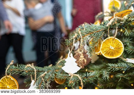 Dried Orange Slices And Tree-shaped Gingerbreads Hanging On A Christmas Tree, With Christmas Lights