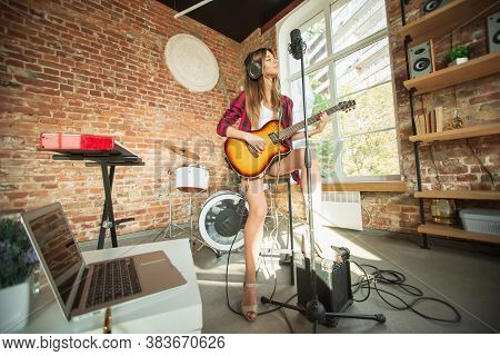 Indie, Rock. Beautiful Woman In Headphones Recording Music, Singing And Playing Guitar While Sitting