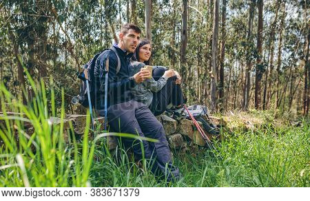 Young Couple Pausing To Eat And Drink While Doing Trekking Outdoors Enjoying Nature