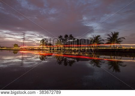 Light Trail Transport Pass The Path In The Morning With Coconut Tree As Background.