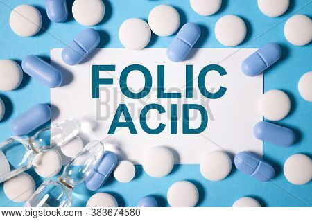 Folic Acid, Text On White Paper On A Blue Background, Top View. White And Blue Tablets And Transpare