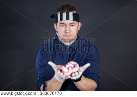 Young Handsome Man Wearing Black And White Bandana With Disgusting And Regret Face Expression Holds