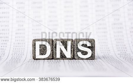 Three Stone Cubes On The Background Of White Financial Statements, Tables With The Word Dns Domain N